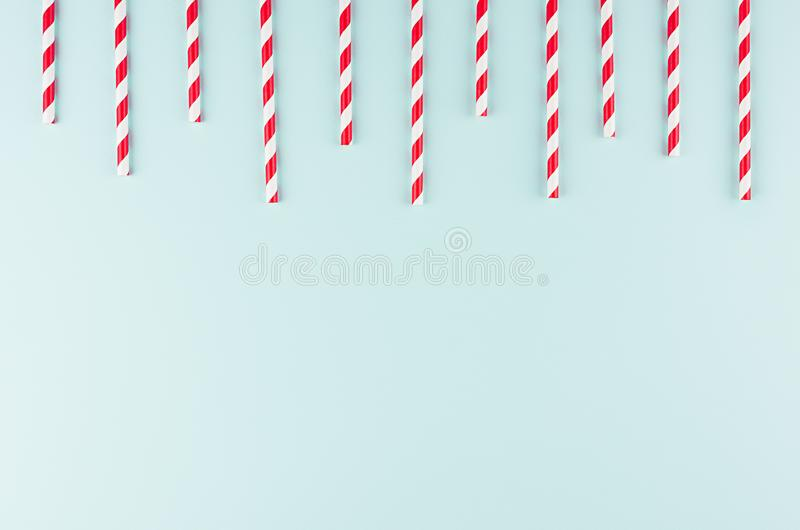 Abstract modern fashion background - red and white striped straws as border pattern on light mint background. Abstract modern fashion background - red and white stock photography