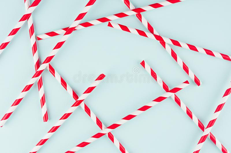 Abstract modern fashion background - red and white striped straws as random pattern on light mint background. Abstract modern fashion background - red and white royalty free stock images