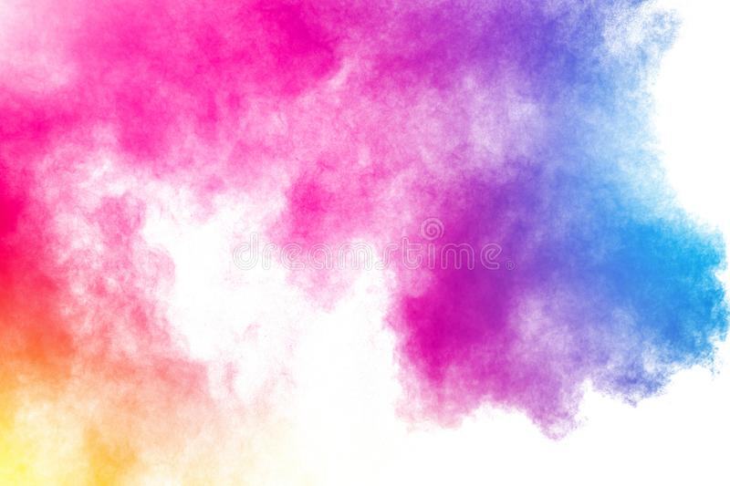 Abstract multi color powder explosion on white background.Freeze motion of dust particles splash royalty free stock image