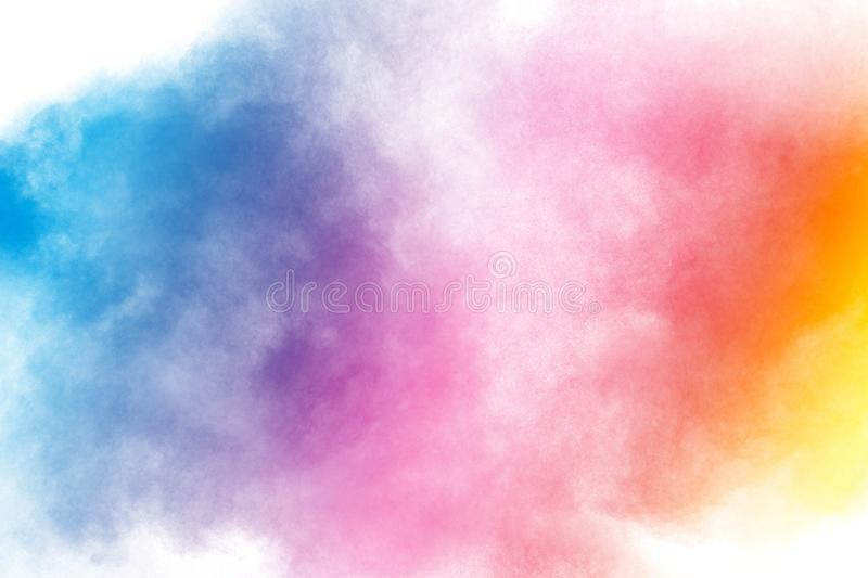 Abstract multi color powder explosion on white background.Freeze motion of dust particles splash stock photo