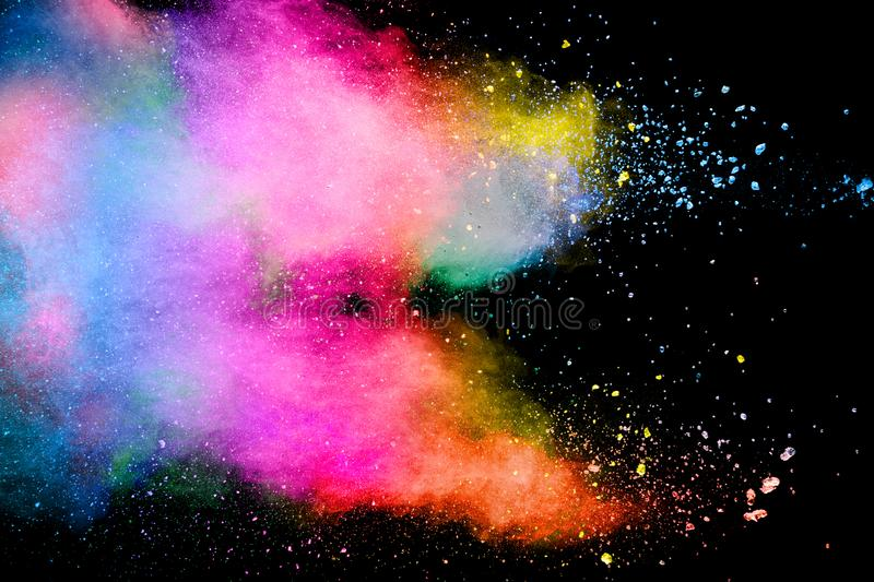 Abstract multicolored powder explosion on black background. Color dust particle splattered on background stock image