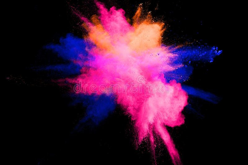 Abstract multicolored powder explosion on black background. Color dust particle splattered on background stock photos