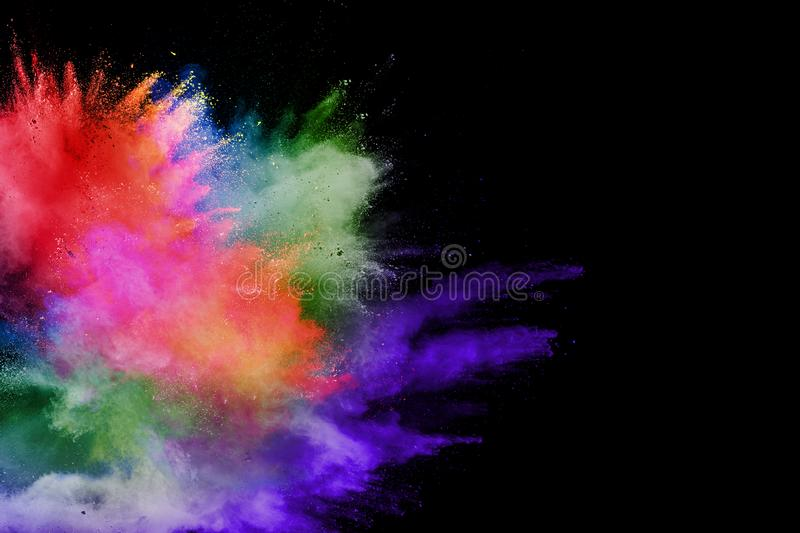 Abstract multicolored powder explosion on black background. Color dust particle splattered on background royalty free stock photography