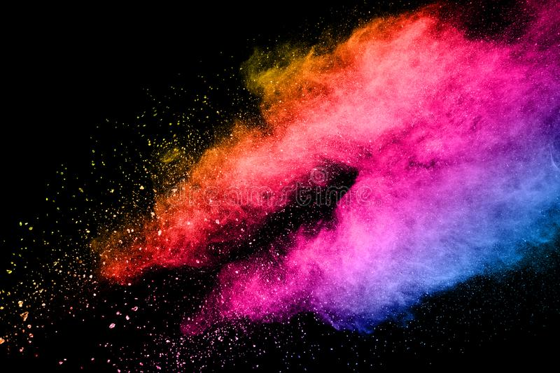 Abstract multicolored powder explosion on black background. Color dust particle splattered on background stock photography