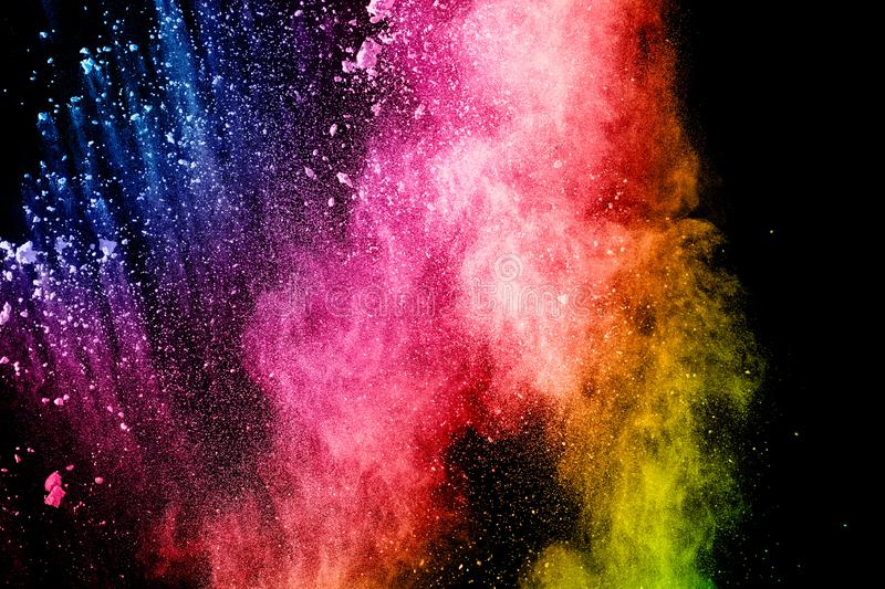 Abstract multicolored powder explosion on black background. Color dust particle splattered on background stock images