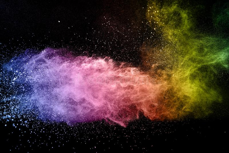 Abstract multicolored powder explosion on black background. Color dust particle splattered on background royalty free stock photo