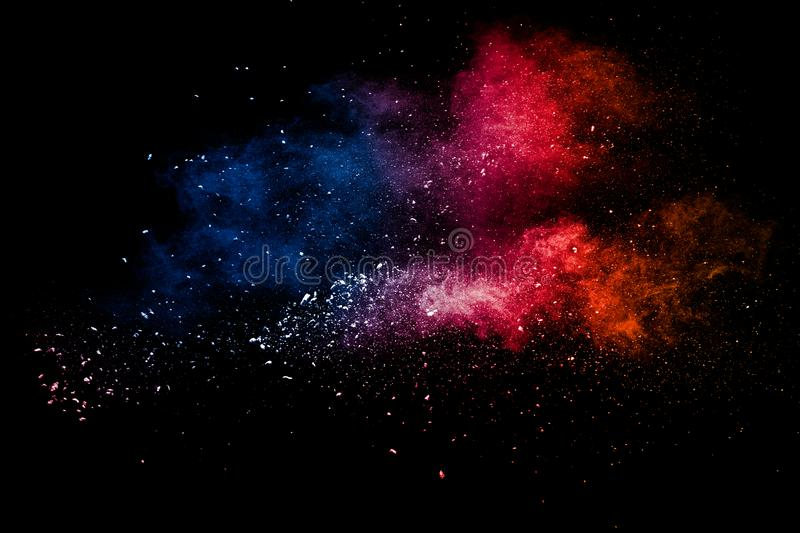 Abstract multicolored powder explosion on black background.Red blue dust particles splatter on background royalty free stock image
