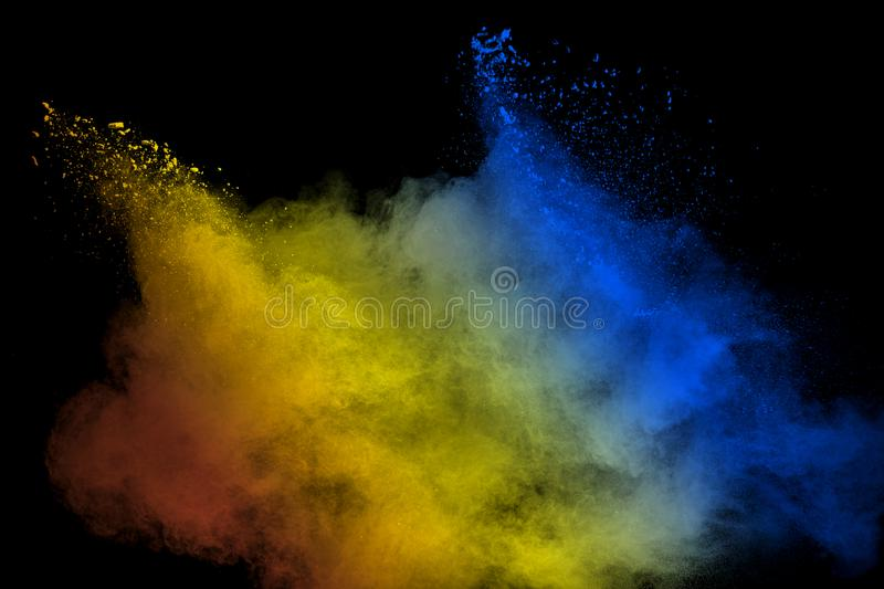 Abstract multicolored powder explosion on black background.Red yellow blue dust particles splatter on background royalty free stock photo
