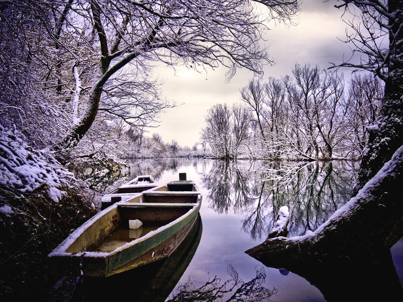Boat and river covered with snow royalty free stock images