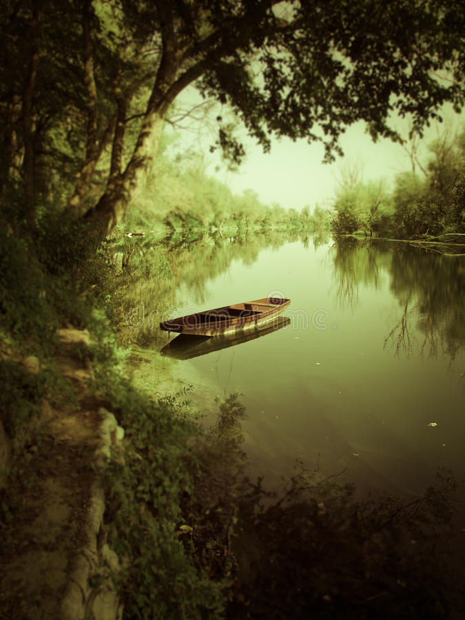 Boat on the river under green shadow royalty free stock photo