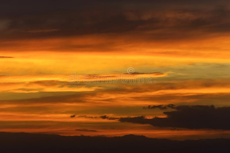 Abstract nature background. Dramatic sunset sky in the clouds saturated with bright colors of orange and yellow royalty free stock photography