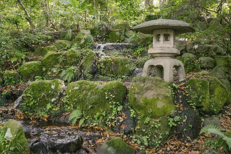 Abstract nature or park background in Japanese style featuring Japanese traditional stone lantern. And decorative waterfall in park in Kanazawa in November royalty free stock image