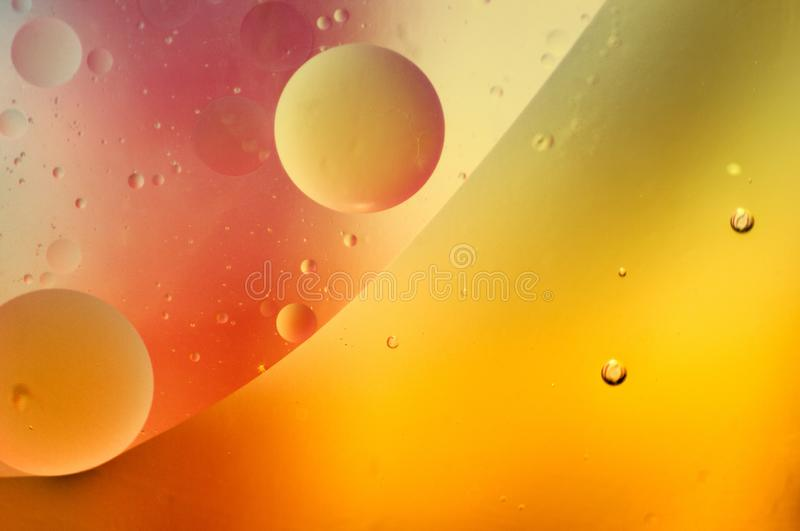 Abstract of olive oil floating on water with yellow, orange and. Coral colors royalty free stock photos