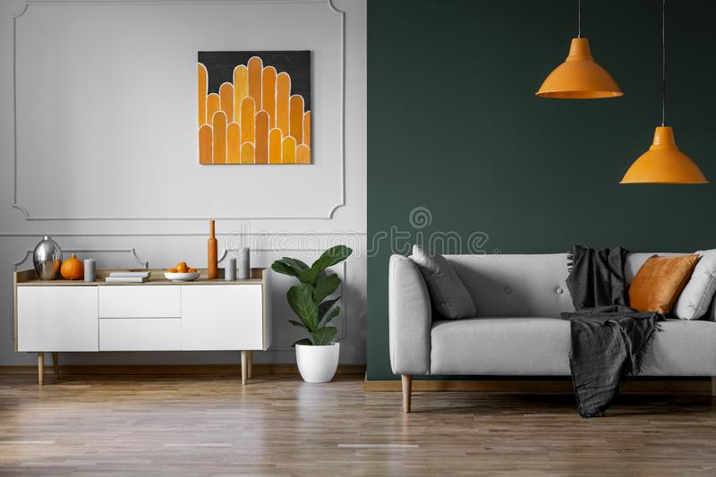 Abstract orange painting on grey wall of stylish living room interior with white wooden furniture and grey couch. Real photo stock photography