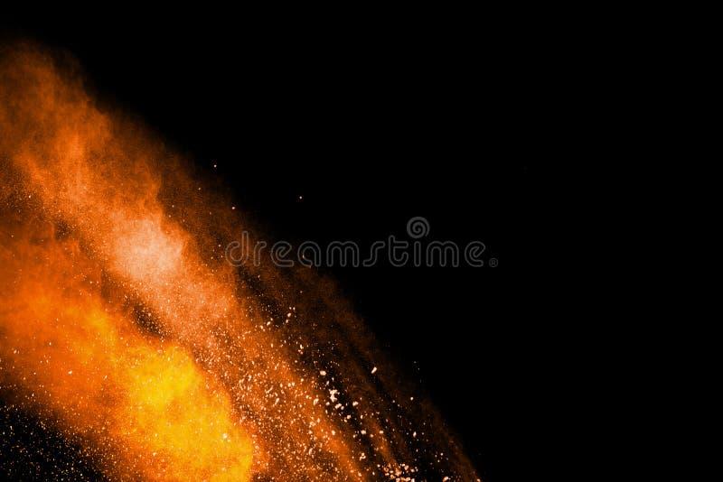 Abstract orange powder explosion on black  background. Freeze motion of orange  dust particles splash.  stock images