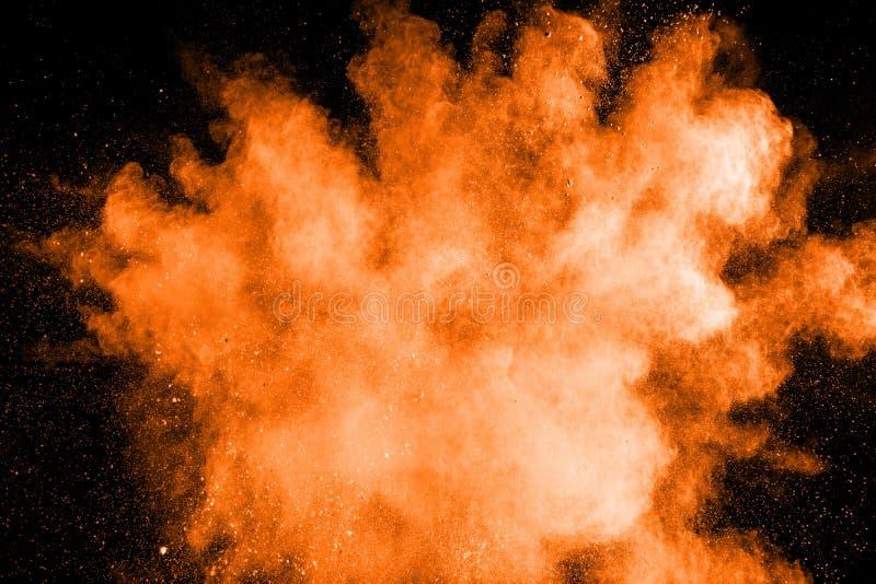 Abstract orange powder explosion on black background.Freeze motion of orange dust splash.  stock images