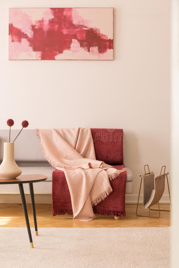 Abstract painting on the empty white wall of elegant living room with grey couch with pastel pink and burgundy blankets royalty free stock image
