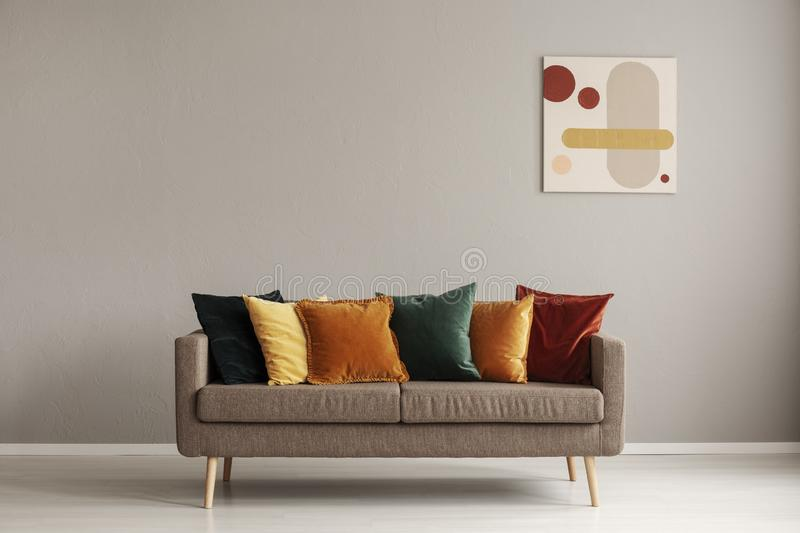 Abstract painting on grey wall of retro living room interior with beige sofa with pillows royalty free stock photography
