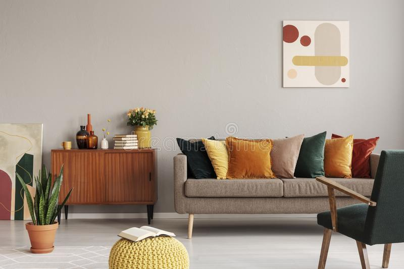 Abstract painting on grey wall of retro living room interior with beige sofa with pillows, vintage dark green armchair and yellow. Pouf with book stock photo