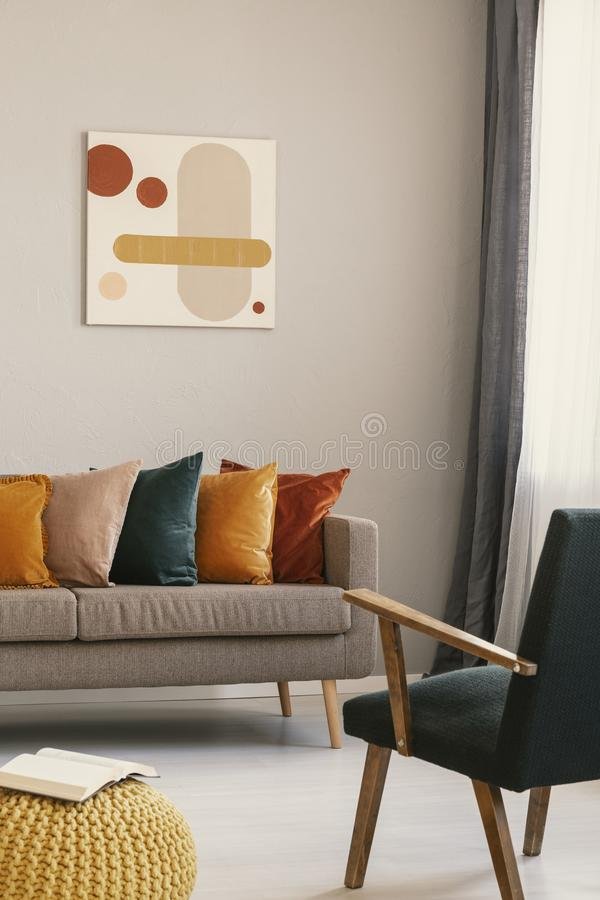 Abstract painting on grey wall of retro living room interior with beige sofa with pillows, vintage dark green armchair and yellow royalty free stock photography