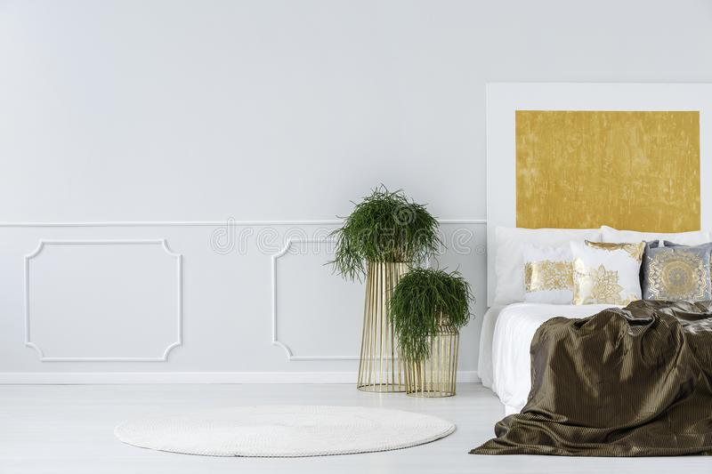 Abstract painting in minimalist bedroom. Potted plants on modern design, golden metal tables next to a cozy double bed in a minimalist bedroom interior with stock image