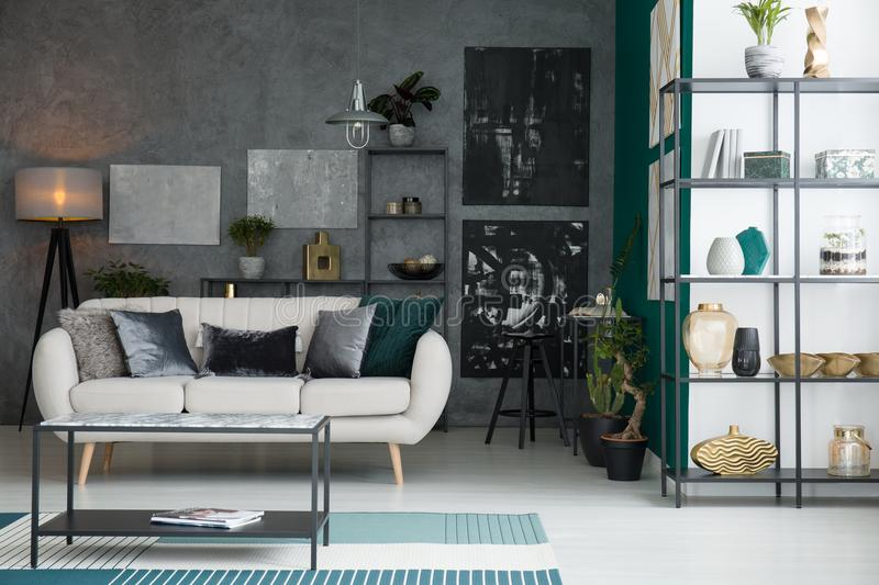 Abstract paintings on raw wall. Black and grey abstract paintings hanging on a raw wall in industrial living room interior with decor and light grey sofa with stock image