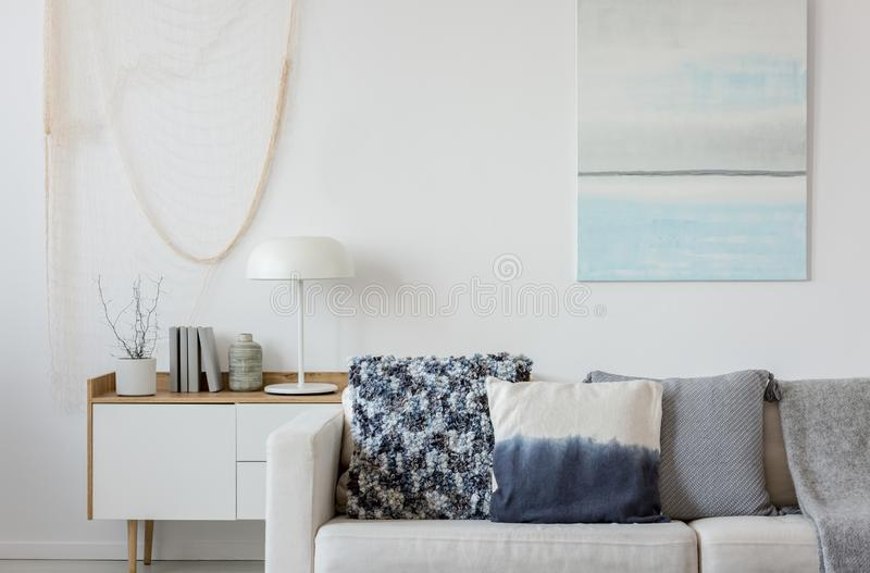 Abstract paste blue and white painting on empty white wall behind beige couch with pillows royalty free stock images