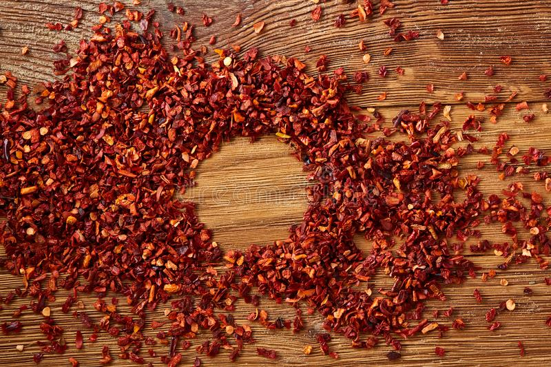 Abstract pattern of dried red hot chilly flakes on rustic wooden background, top view, close-up, macro, selective focus. royalty free stock photography