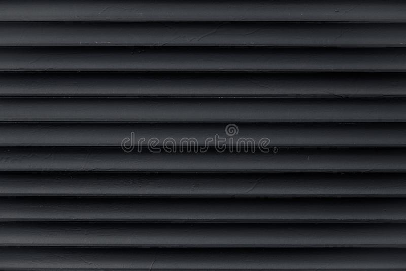 Abstract pattern of lines. Texture of black corrugated metallic surface. Dark ribbed background with stripes, straight lines. Mode royalty free stock photography