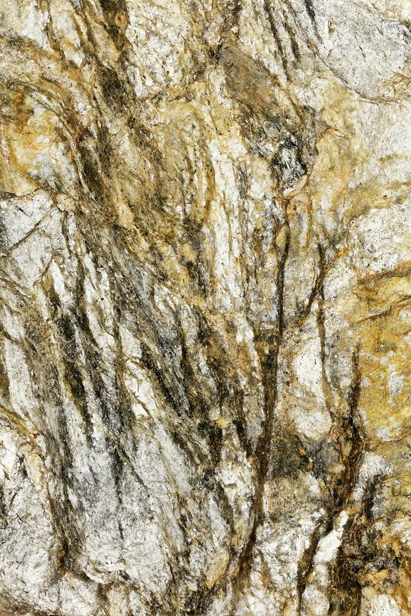 Abstract Pattern on lump of golden Rock. Closeup of piece of stone found in the austrian alps looks like abstract painting or prehistoric painting in caves royalty free stock photography