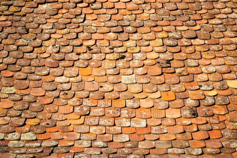 Abstract pattern of old, traditional, brown/orange, ceramic, overlapping shingles tiles, schindle/schindel in German on a roof royalty free stock photos
