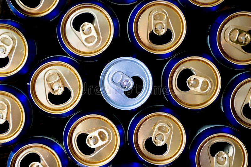 Abstract pattern of opened aluminium cans, top view. One white soda or beer can standing out among yellow and blue cans. royalty free stock photography