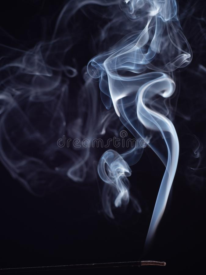 Abstract pattern of white smoke from burning incense, isolated on black background, close up view. Abstract background. Smoke brush. Eastern fragrance for royalty free stock photo