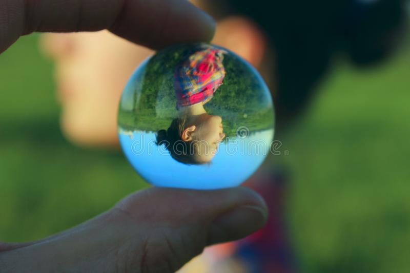Abstract People. People, Travel Concept. Female Fingers Holding Crystal Ball Outdoors. royalty free stock photos