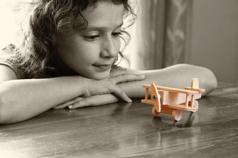 Abstract photo of cute kid looking at old wooden plane. selective focus. inspiration and childhood concept stock photography