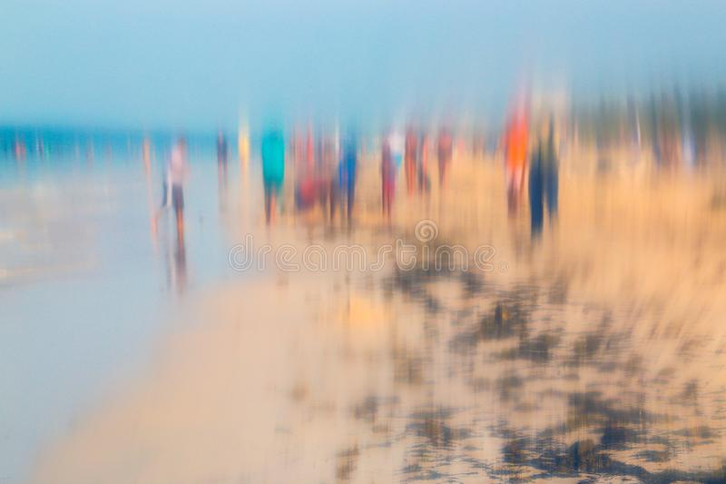 Abstract photo of people walking on the beach in the colorful impressionist style effect. Soft focus. A blurring technique creates a unique impressionist style royalty free stock image