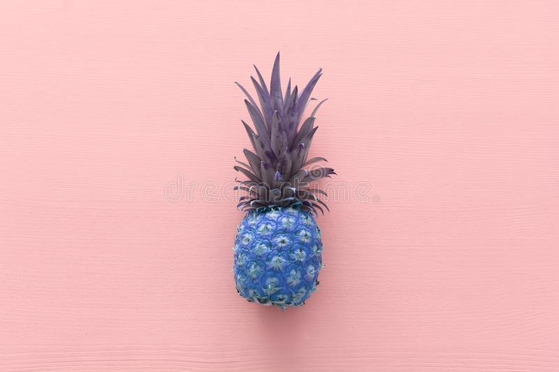 Abstract photo of purple pineapple over pink wooden background. Beach and tropical theme. Top view.  royalty free stock photography