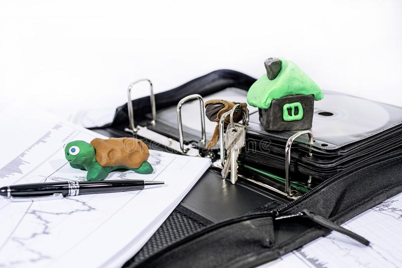 Abstract photo of slow property buying process. Documents case with turtle. stock photos