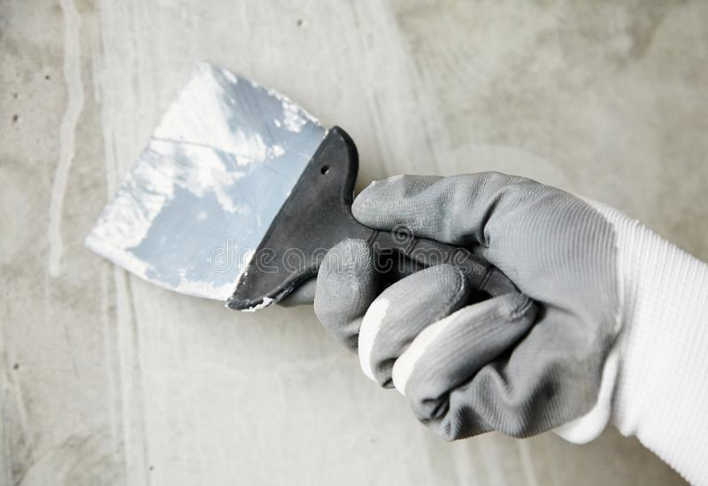 abstract photo of wall finishing work, trowel in the hands of a worker at a construction site royalty free stock photo