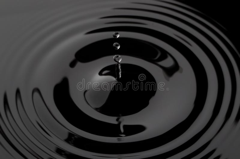 Droplets of black water dark liquid ripples with cool looking scene royalty free stock images