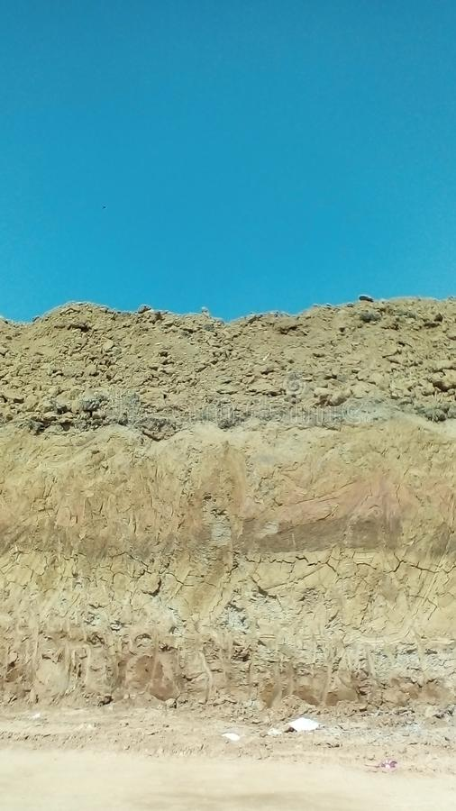 Abstract picture of different layers of soil under the blue sky in a dig area. stock photos