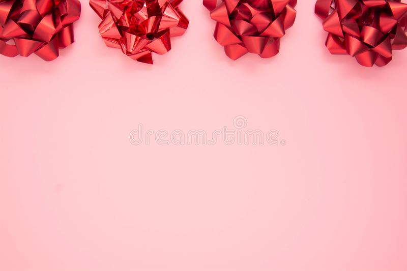 Abstract pink background with red gift ribbon bows. Valentine's Day, Love, birthday royalty free stock photo
