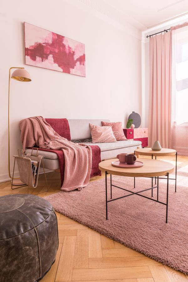 Abstract pink and burgundy painting on the empty wall of trendy native colors interior with stylish settee royalty free stock image