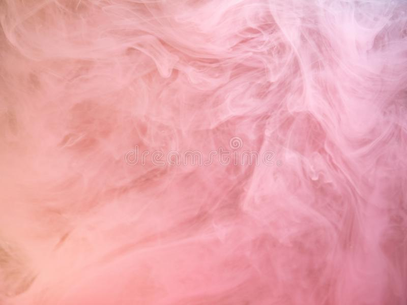 Abstract pink smoke swirling under water, close up view. Blurred background. Acrylic paint dissolving into water. Abstract pattern. Pink ink dropped into royalty free stock photo