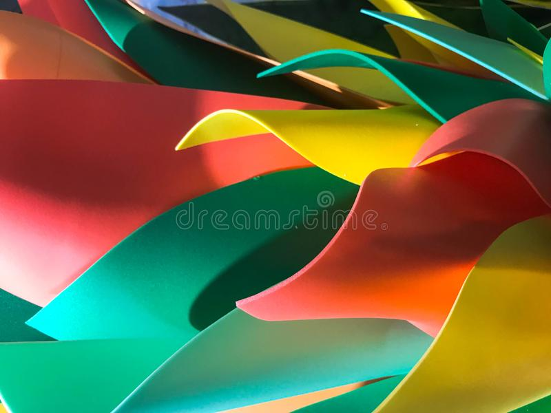 Abstract plastic artificial multicolored shiny festive cheerful beautiful joyful petals leaves. Background, texture stock image