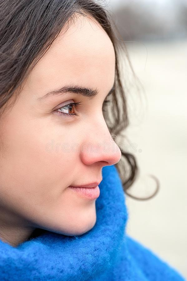 Abstract portrait of young beautiful girl with sad and adorable eyes with sensitive look in the cold day and blue scarf extremely. Close up vertical stock photos
