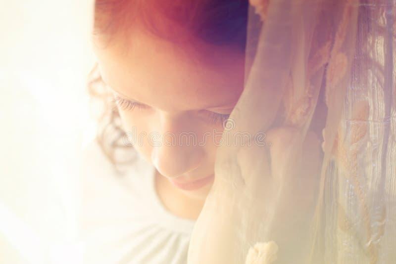Abstract portret van nadenkend meisje dichtbij venster retro gefiltreerd beeld stock fotografie