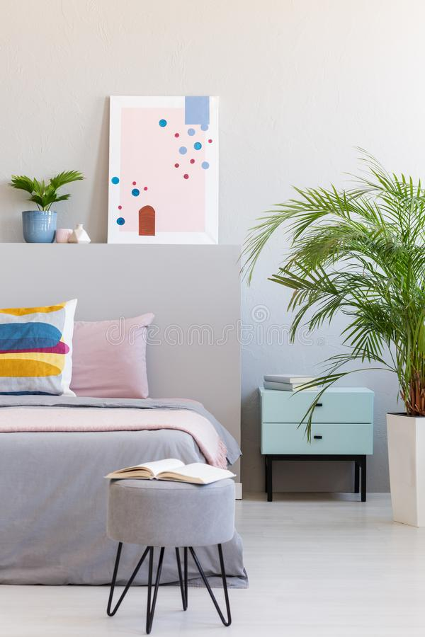 Abstract poster in real photo of bright bedroom interior with op. En book on hairpin pouf, fresh plants and bedside table concept royalty free stock photo