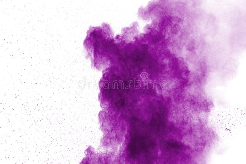 Abstract purple powder explosion on white background. Freeze motion of purple dust splash stock photography