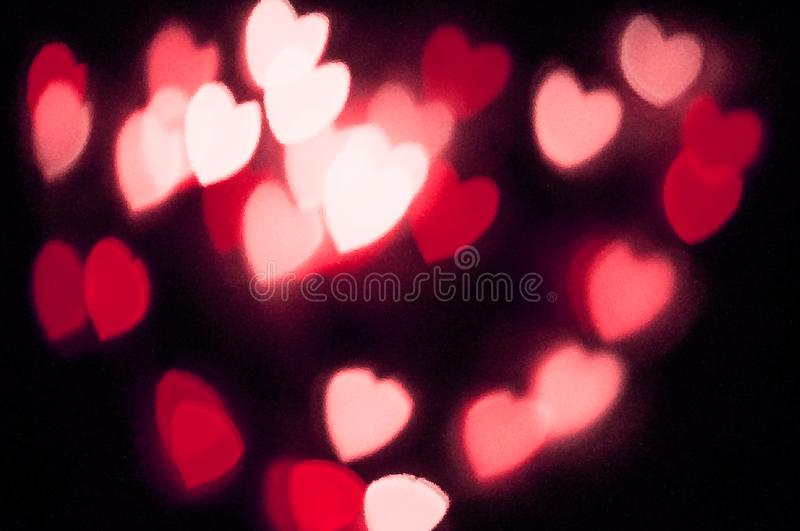 Abstract red heart bokeh vision bright fantasy on black background design in red frame with red heart, illuminated light effect. Valentines day background royalty free stock image